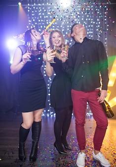 세 명의 젊은 남성과 두 명의 여성이 후드를 쓰고 유리 샴페인을 들고 생일을 축하하며 나이트클럽에서 파티를 즐겨요