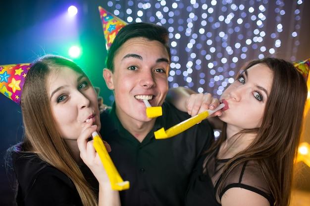 세 명의 젊은 남성과 두 명의 여성이 후드를 쓰고 파이프를 들고 생일을 축하하며 나이트클럽에서 파티를 즐기며 즐거운 시간을 보낸다