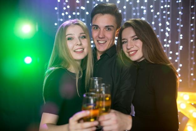 세 명의 젊은 남성과 두 명의 여성이 유리 샴페인을 들고 생일을 축하하며 파티의 나이트클럽에서 즐거운 시간을 보낸다