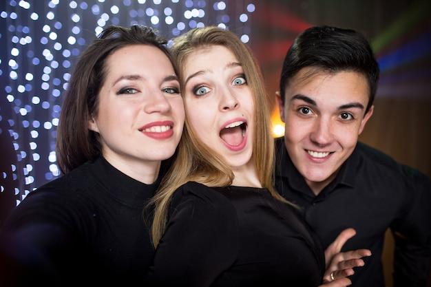 유리 샴페인을 든 세 명의 젊은 남성과 두 명의 여성이 스마트폰으로 셀카 사진을 찍으며 생일을 축하하며 파티의 나이트클럽에서 즐거운 시간을 보낸다