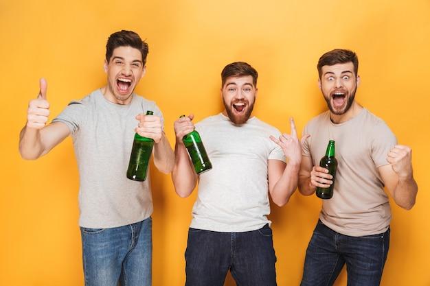 Трое молодых людей пьют пиво и празднуют