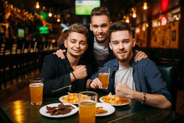Трое молодых людей позируют за столом с пивом, чипсами и крекерами, интерьер спорт-бара, счастливая дружба футбольных фанатов