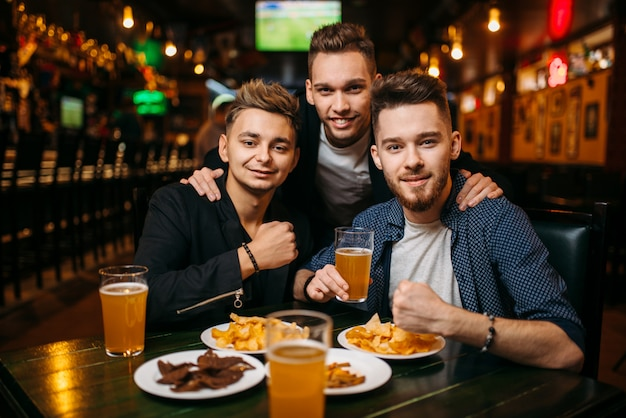 Three young men poses at the table with beer, crisps and crackers, sport bar interior, happy friendship of football fans