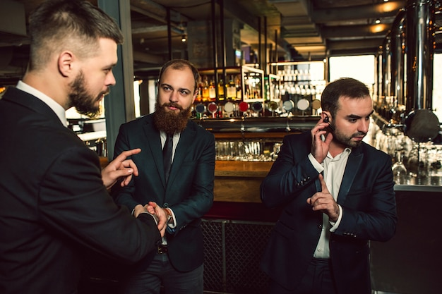 Three young men stand in pub. one hold hand on headphone. he show finger up. second young man look at first and try to toalk. third guy look at second one.