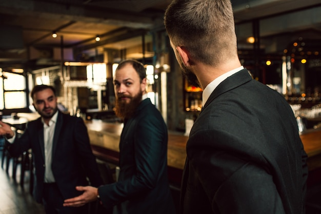 Three young men in suits lok at each other. one of them stand with back to camera. office workers stand in pub.