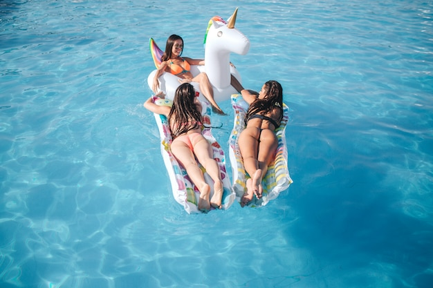 Three young models posing in swimming pool. they lying on floats. two women show their amazing shapes of body. third model chilling and look at her friends.