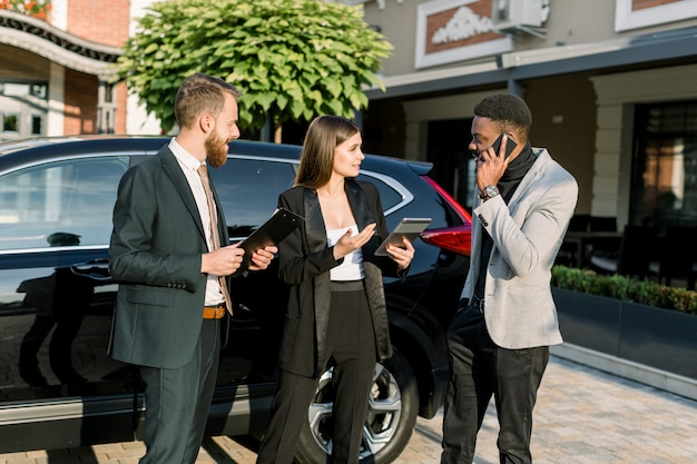 Три молодых многонациональных деловых людей обсуждают что-то на открытом воздухе возле черного автомобиля. кавказские женщины держат планшет, африканский мужчина разговаривает по телефону и кавказский мужчина держит деловые контракты