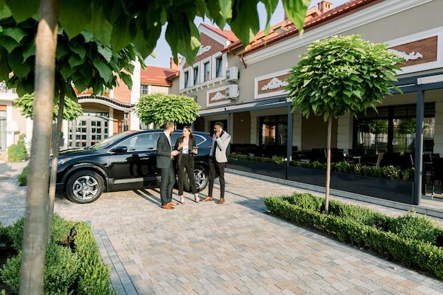 Трое молодых многорасовых коллег по бизнесу рассказывают о рабочей встрече, стоя на улице возле черного кроссовера во дворе бизнес-центра