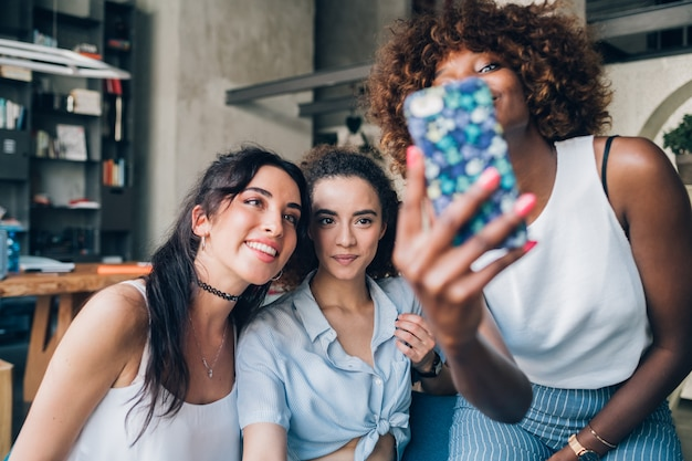 Three young multiracial friends looking the smartphone and sitting together