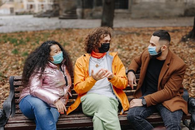 医療用マスクの木製ベンチに座って、笑顔で話している3人の若い多民族の友人。秋の公園で一緒に過ごす時間を楽しむ男女。