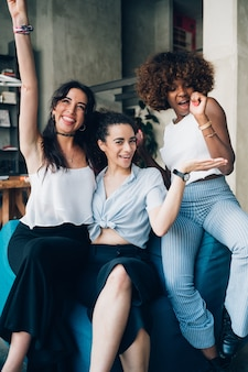 Three young multiracial women having fun and posing together in modern loft