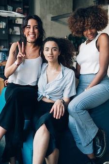 Three young multiracial women sitting together in modern loft and looking