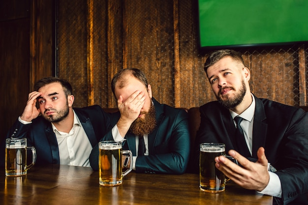 Three young office workers in suits sit at table in bar. they watch football game. guy on middle cover face with hand. they all are emotional.