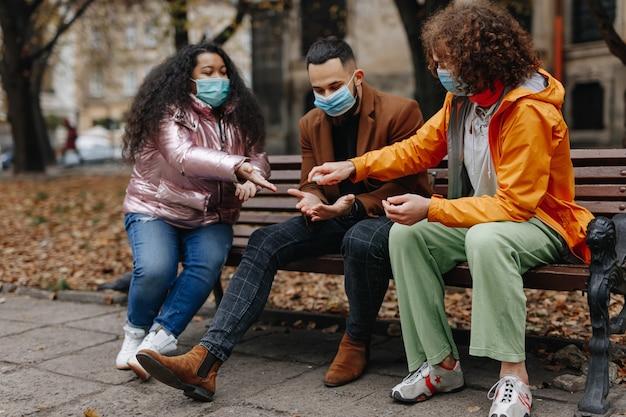木製のベンチに座って消毒剤を適用する医療用フェイスマスクの3人の若者。パンデミックの時間と検疫措置。