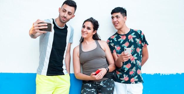 Трое молодых людей в летней одежде на бело-синей стене с помощью своих смартфонов