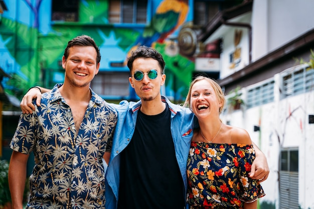 서로 뒤에서 서로 껴안고 거리 예술로 장식 된 컬러 파사드가있는 거리 한가운데에서 웃고있는 서로 다른 민족의 세 젊은이