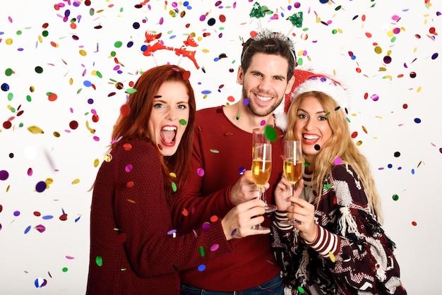 Tre giovani tostatura con champagne su sfondo bianco
