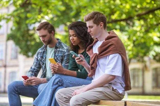 Трое молодых людей со смартфонами в руках проводят время в парке