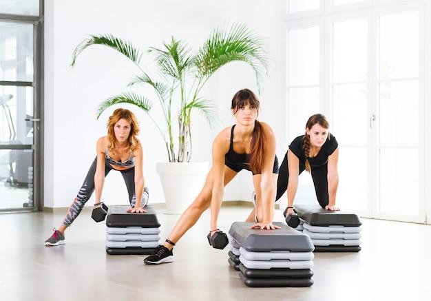 Трое молодых людей занимаются фитнесом с гантелями