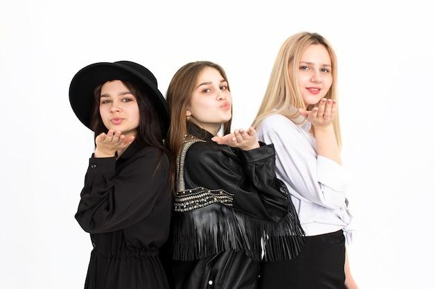 3人の若い可愛い女の子がキスを吹きます。白い背景の上の写真