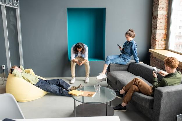 세 젊은 편안한 디자이너 또는 모바일 응용 프로그램 개발자가 노란색 안락 의자에 누워있는 동안 스마트 폰에서 스크롤