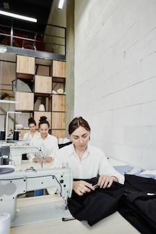 新しいファッションコレクションやクライアントの注文で一緒に働いている間、電気ミシンのそばに並んで座っている3人の若いシームレス