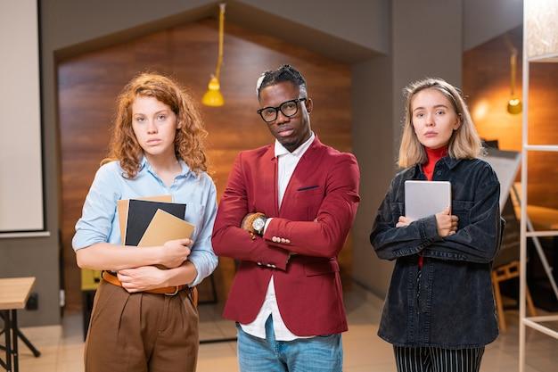 Трое молодых серьезных мультикультурных студентов в повседневной одежде стоят в ряд в современном кафе после уроков