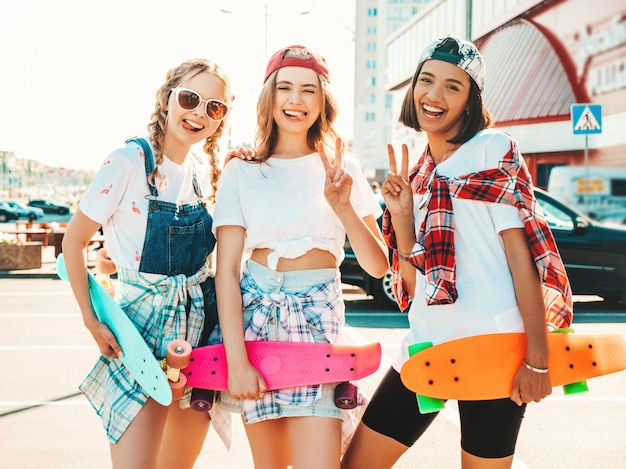 Три молодые улыбающиеся красивые девушки с красочными пенни скейтборды. женщины в летней одежде битник позирует на фоне улицы. позитивные модели с удовольствием и схожу с ума. покажите знак мира
