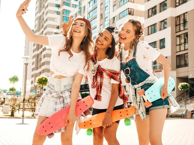 カラフルなペニースケートボードと3人の若い笑顔の美しい女の子。通りの背景でポーズをとって夏の流行に敏感な服を着た女性。セルフポートレート写真を撮る肯定的なモデル