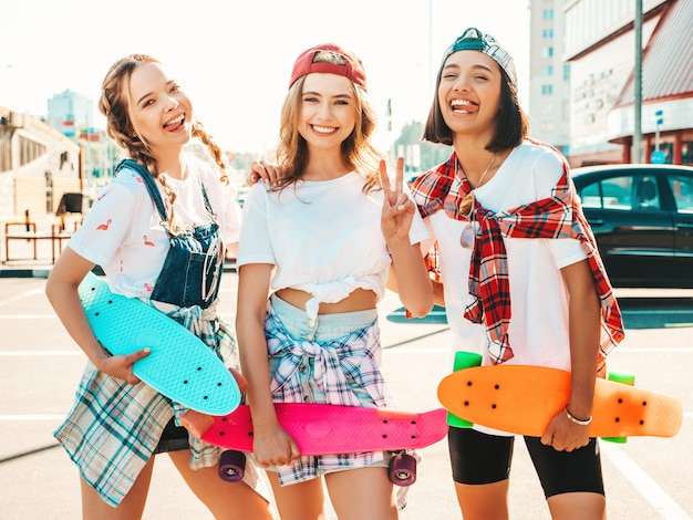 Three young smiling beautiful girls with colorful penny skateboards.