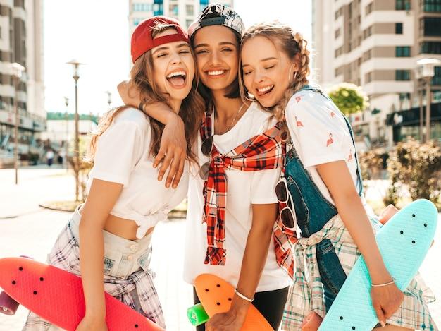 Три молодые улыбающиеся красивые девушки с красочными пенни скейтборды.