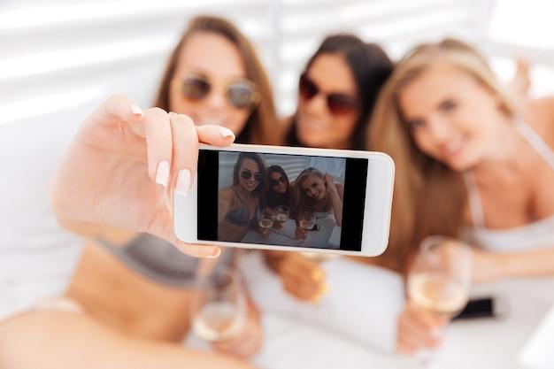 Три молодые улыбающиеся счастливые девушки делают селфи, держа очки с напитками