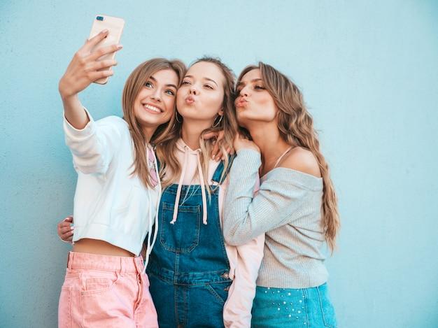 여름 옷에 세 젊은 웃는 힙 스터 여성. 소녀는 스마트 폰 selfie 셀프 초상화 사진을 찍고.