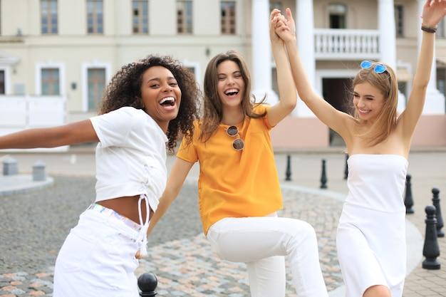 Три молодых улыбающихся хипстерских женщины в летней одежде, позирует на улице. женщина, показывающая положительные эмоции лица. танцы.