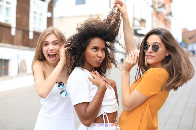 Три молодых улыбающихся хипстерских женщины в летней одежде, позирует на улице. женщина, показывающая положительные эмоции лица.