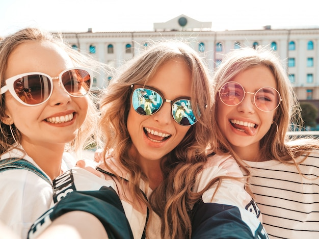 Three young smiling hipster women in summer clothes.girls taking selfie self portrait photos on smartphone.models posing in the street.female showing positive face emotions in sunglasses