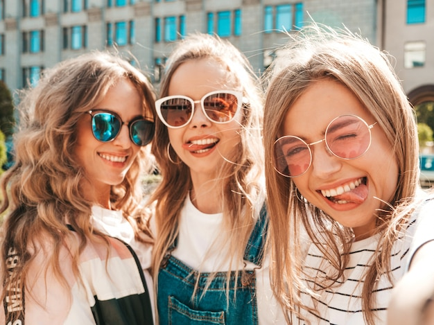 Three young smiling hipster women in summer clothes.girls taking selfie self portrait photos on smartphone.models posing in the street.female showing positive face emotions.they show tongue