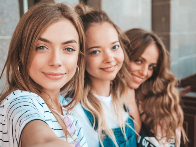 Three young smiling hipster women in summer clothes.girls taking selfie self portrait photos on smartphone.models posing in the street.female showing positive face emotions