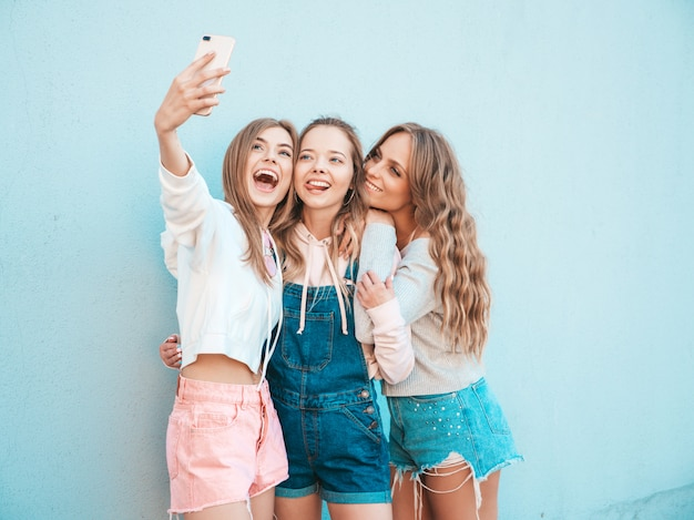 Three young smiling hipster women in summer clothes.girls taking selfie self portrait photos on smartphone.models posing in the street near wall.female showing positive face emotions.showing tongue