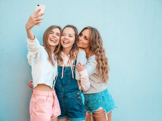Three young smiling hipster women in summer clothes.girls taking selfie self portrait photos on smartphone.models posing in the street near wall.female showing positive face emotions.shows tongue