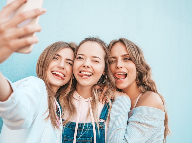 Three young smiling hipster women in summer clothes.girls taking selfie self portrait photos on smartphone.models posing in the street near wall.female showing positive face emotions