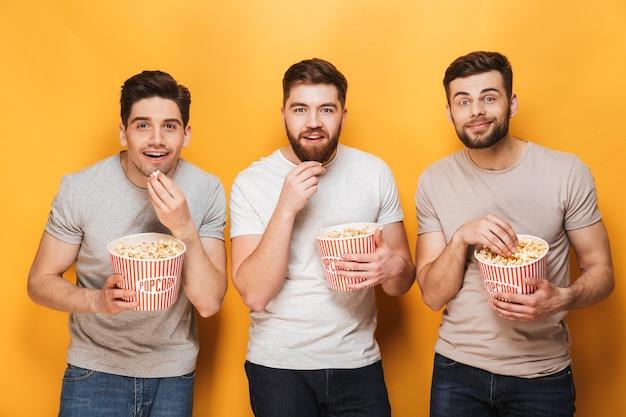 ポップコーンを食べて笑顔の3人の若い男性