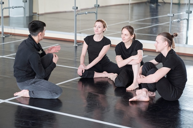 Three young students of dance course looking at their groupmate during discussion of basic exercises at break after training