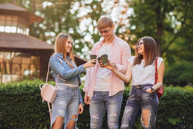 Трое молодых студентов, две красивые девушки и красивый парень стоят и пьют кофе в кампусе.