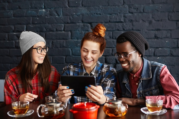 Three young stylish people of different races watching videos online on generic digital tablet while dining together at restaurant