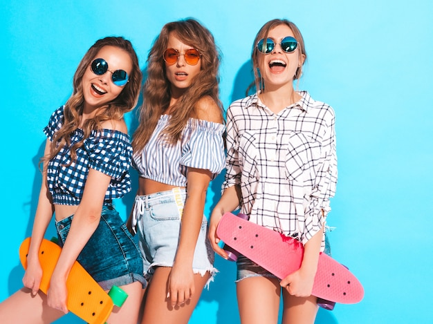 Three young stylish sexy smiling beautiful girls with colorful penny skateboards. women in summer checkered shirt clothes in sunglasses. positive models having fun