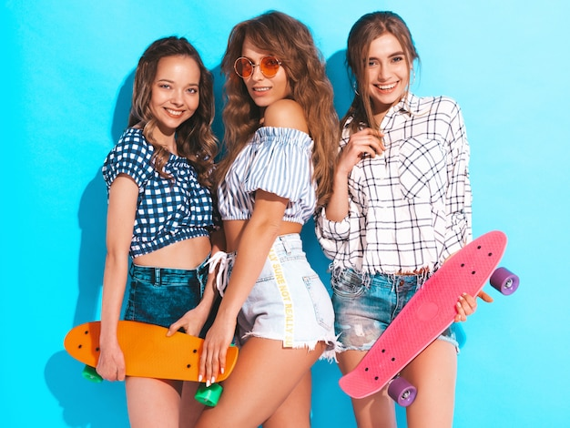 Three young stylish smiling beautiful girls with colorful penny skateboards. woman in summer checkered shirt clothes posing. positive models having fun