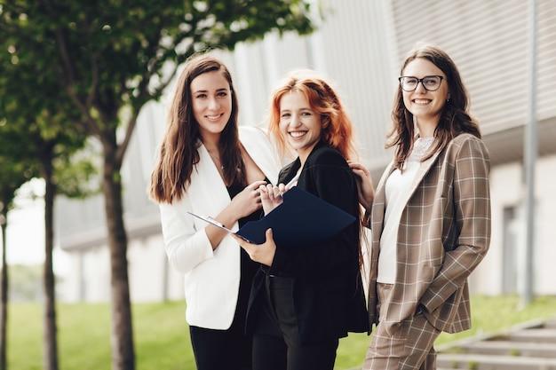 屋外で作業して笑顔の3人のスタイリッシュな若い女性