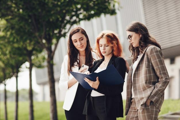 Три молодые стильные женщины, работающие на открытом воздухе