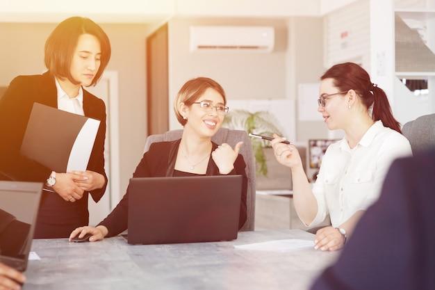 사무실에서 세 명의 성공적인 비즈니스 여성이 함께 즐겁게 프로젝트를 진행하고 있습니다.